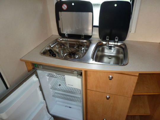 Küche mit Kühlschrank, Kochfeld und Spüle - WasserCamper Motorkatamaran Speedy XL 833 mit Sterckeman Wohnwagen Starlett 370.