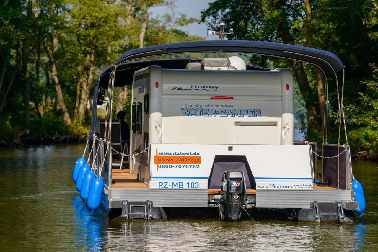 Wassercamper | Heckansicht mit breitem umlaufenden Gang und sparsamen Aussenborder | Camping auf dem Wasser